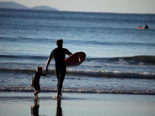 Su Nido Inn image of father and child surfing together